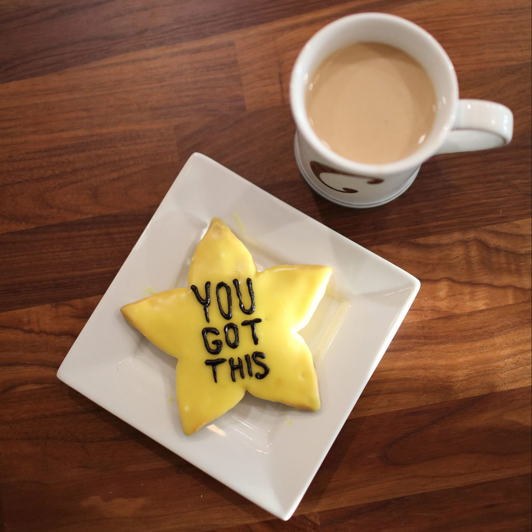 """""""You Got This"""" written in icing on a star shaped sugar cookie with mug of coffee."""
